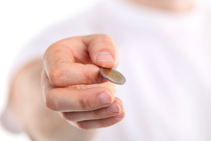 Young caucasian man holding a two euro coin